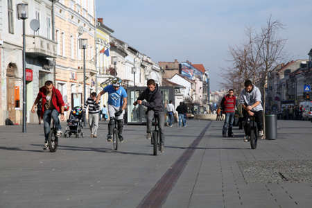 young men riding monocycles on a street in romania Editorial