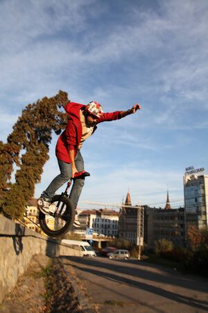 young man making a dangerous jump on a monocycle
