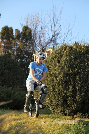 young man comming down a hill on a monocycle