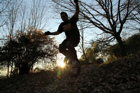 irresponsible: young man comming down a hill on a monocycle