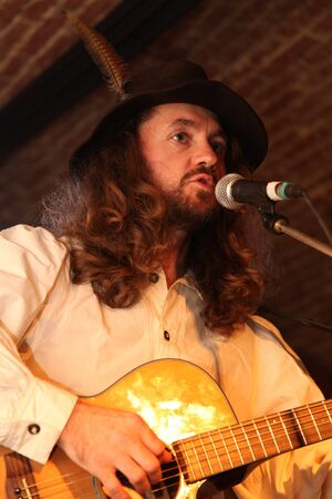 man with hat and feather singing live at a concert in romania