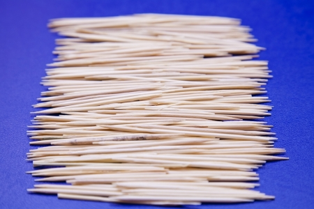 many wooden toothpicks on a blue background