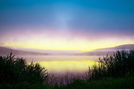 Misty lake at sunrise with fog rising from the water photo