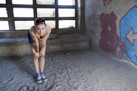 young woman staring at the camera in an abandoned warehouse on a dusty old floor