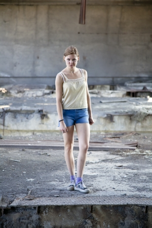 Young beautiful woman in an abandoned old wrecked building staring