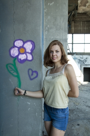 young woman holding a drawing of a flower on a wall in an abandoned building