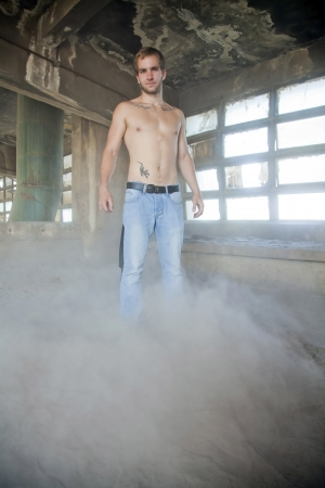young beautiful athletic man sitting in a dusty room with no t-shirt photo