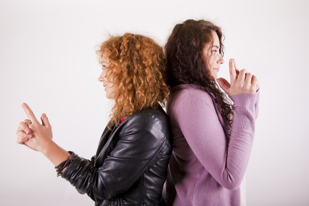 two women froends standing back to back with hands like pistols Stock Photo
