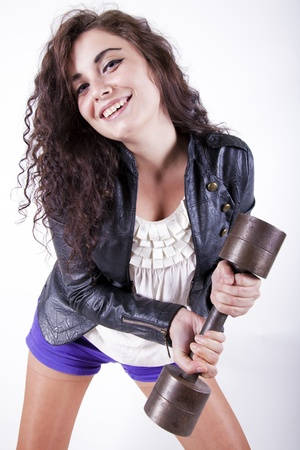 Young atrractive woman holding a weight having fun and smiling photo