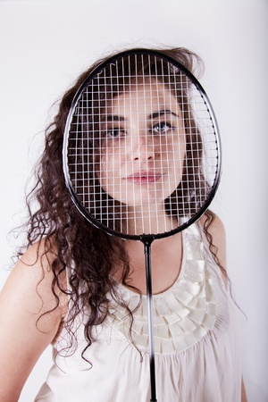 young atractive brunnet young woman holdin a tennis racket over her face
