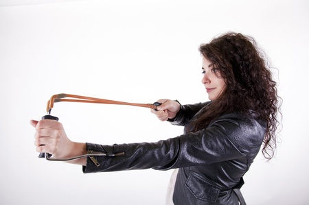 spanned: brunette young girl holding a slingshot aiming on the left side Stock Photo