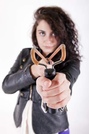 spanned: brunette young girl holding a slingshot aiming at the camera looking angry
