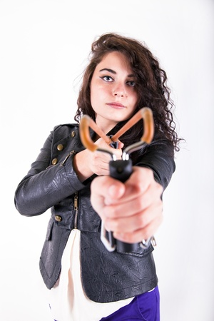 brunette young girl holding a slingshot aiming at the camera looking angry