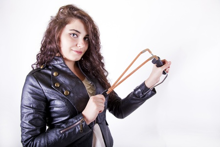 brunette young girl holding a slingshot aiming at the camera smilling
