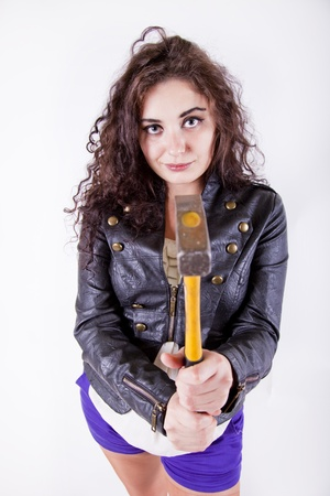 Young woman holding a hammer pointing at the camera readin for work photo