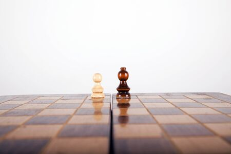 chess pawn going head to head with a horse on a white nackground