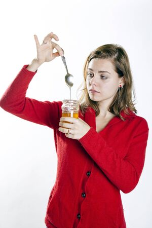 young woman holding a jar of honey and a spoon looking at it Stock Photo - 15784571
