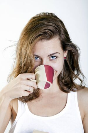young preety woman drinking a cup of coffe and smiling to the camera Stock Photo - 15810033