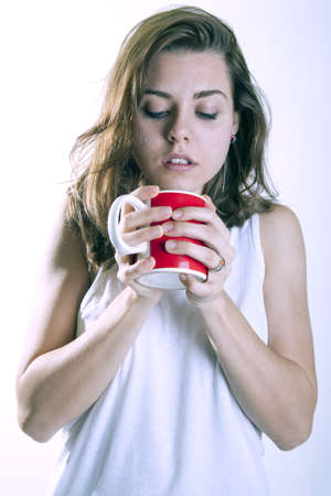 young woman drinking a cup of coffeein the morning pijamas