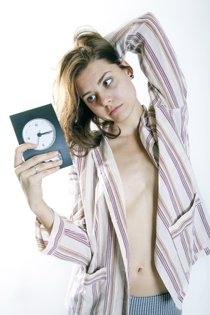 woman in pijamas sad in the morning holding a clock Stock Photo - 15811406