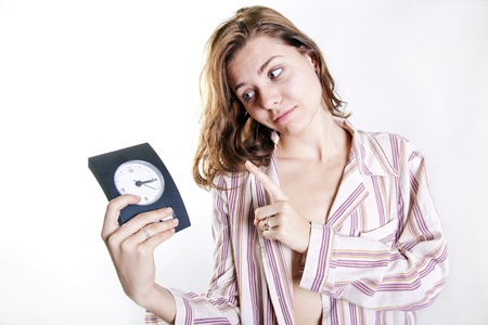 young attractive woman begging for one minute of sleep with clock in her hand Stock Photo - 15811399