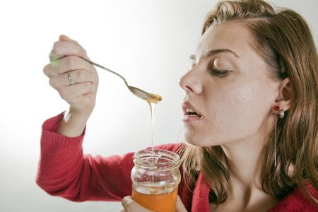 young beautifull woman eating honey with a spoon from a jar Stock Photo - 15811405