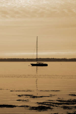 sepia toned boat alone off shore at sunset