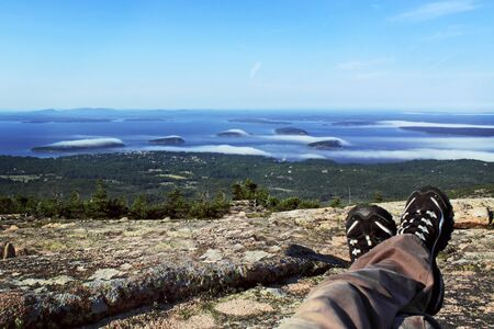 man feet with a stunning view of mountains and ocea Stock Photo - 17365376