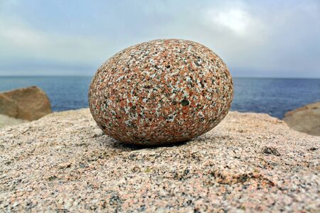 single round grainny stone on the atlantic ocean shore with clouds on the background Stock Photo - 17375972