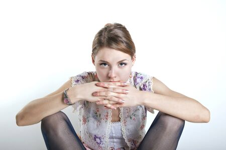 young gorgeous woman staring at the camera with hands over mouth photo