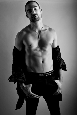 open shirt: young sexy man posing with uunbuttoned shirt on black and white background Stock Photo