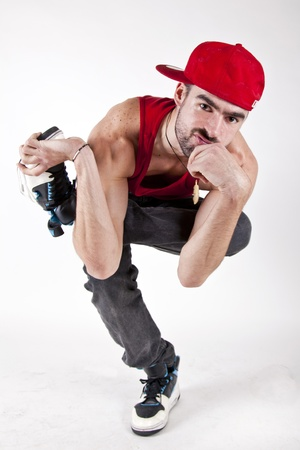 young man bboy sitting serious with red cap on one foot