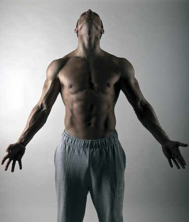 very muscular body builder athlete holding his head high and arms wide open