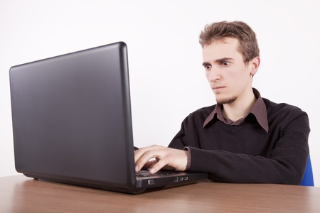 young man with froun on his face usind a laptop at a desk Stock Photo