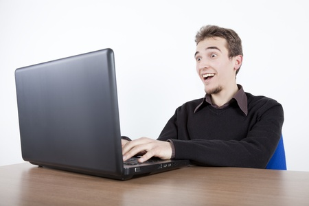 young business man with laptop at a desk surprised and happy with a  big smile photo
