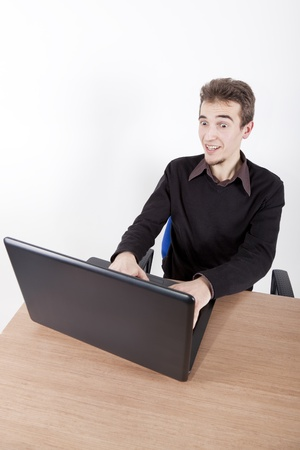 surprised young man with laptop smilling at a desk in an office chair