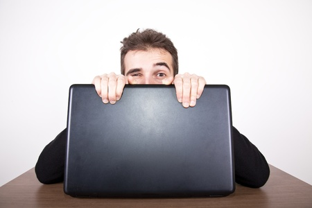 Young man sitting behind a laptop winking with one eye and gripping hard on the screedn Stock Photo