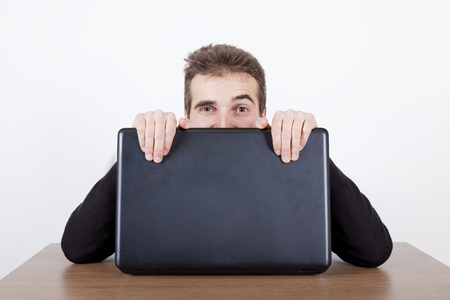 young man hiding behind a laptop on a desk