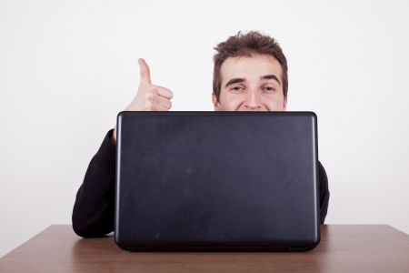 young man with laptop hjolding up his thumb from behind his laptop