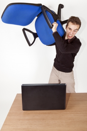 isolated angry bussiness man with office chair in his hand above his head ready to destroy a laptop