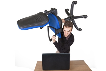 young angry man standing above a laptop with an office chair preparing to destroy it photo