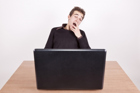 overwrought: sleepy young man yawning at a desk with a laptop in front of him