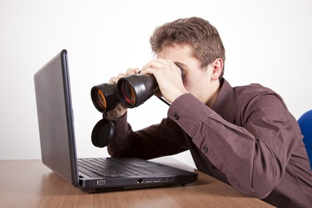 young man searching on the web at a laptop with binoculars