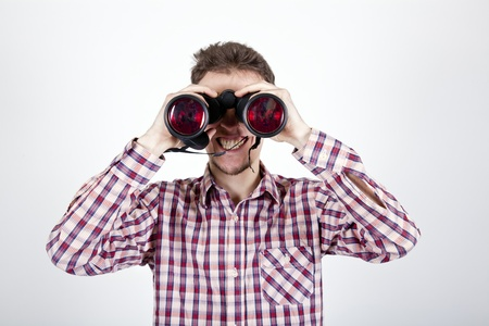 young man looking with binoculars at you photo