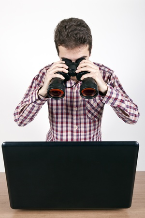 man looking at a laptop with binoculars