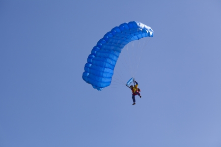 man with parachute flying on a clear blue perfect sky