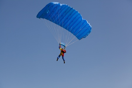 man on clear blue sky with parachute from behind