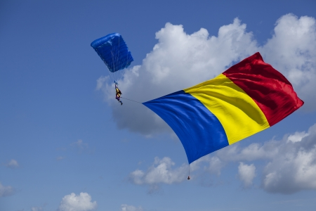 parachute skydiver with huge romanian flag hanging from him
