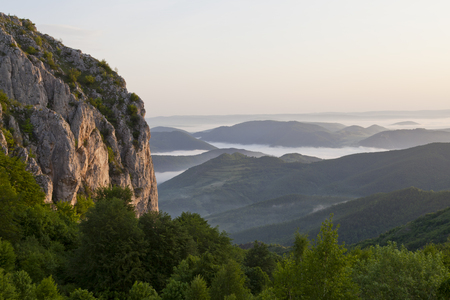 ridgeline: mountain with mist and green forest at sunrise