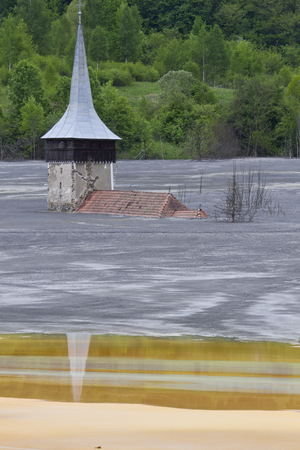 inundated: Flooded church in poluted mud lake in transilvania
